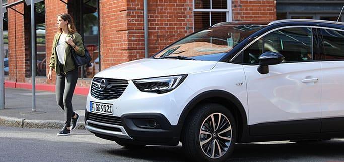 Tjej går förbi parkerad Opel
